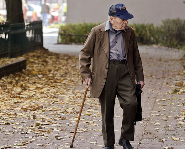 Elderly man walking on pavement