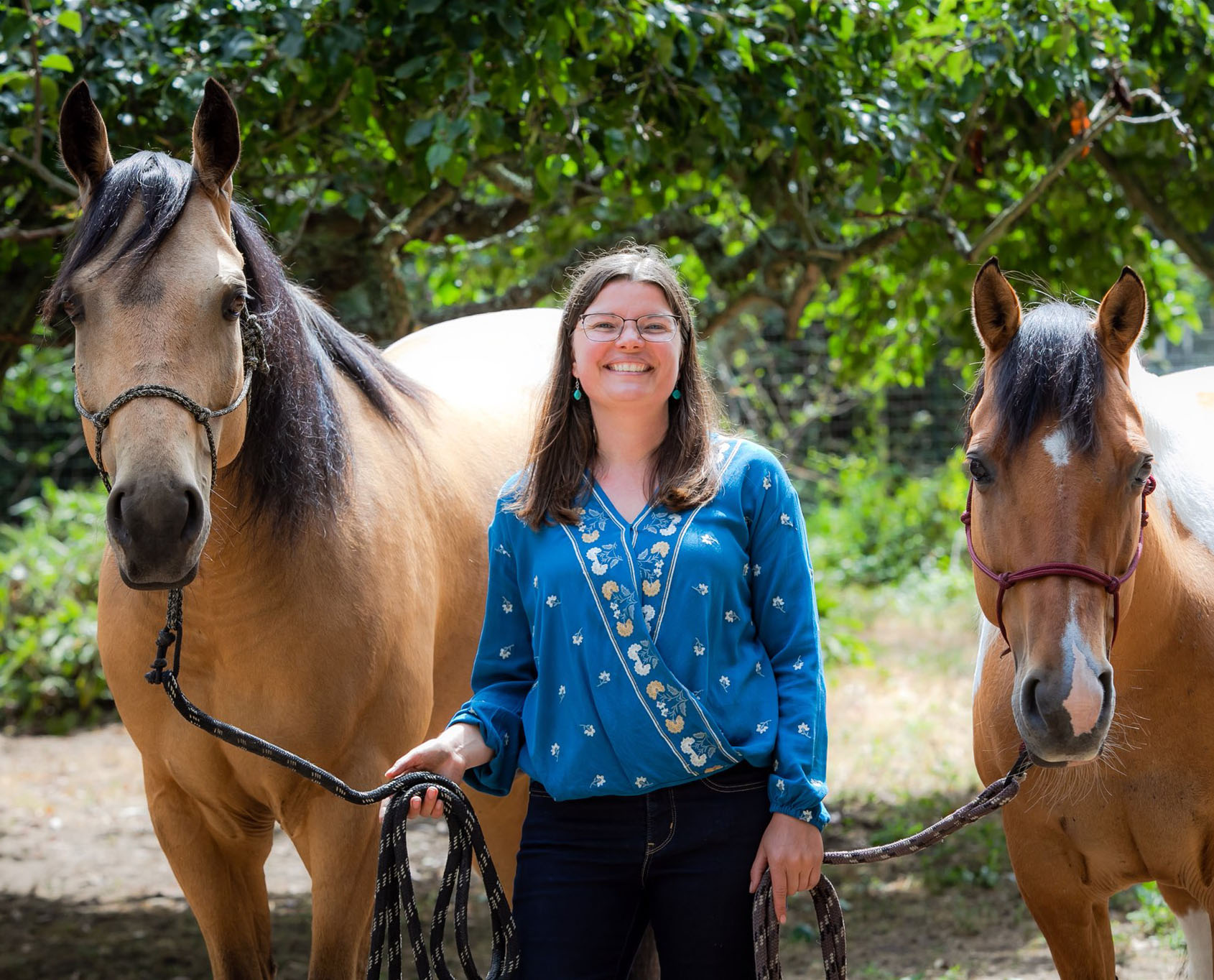 woman smiling and standing between two horses at a therapeutic ranch