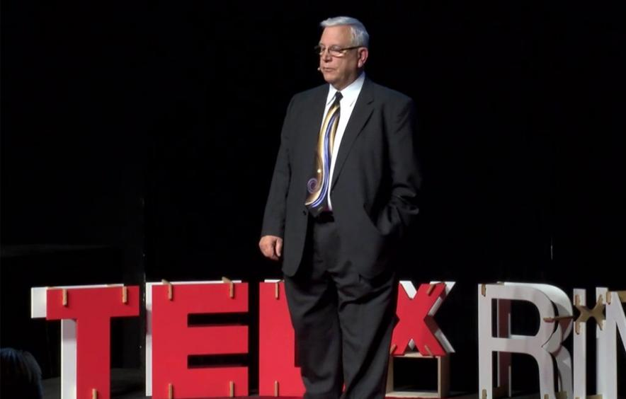 Donald Burnes standing on TED Talk stage