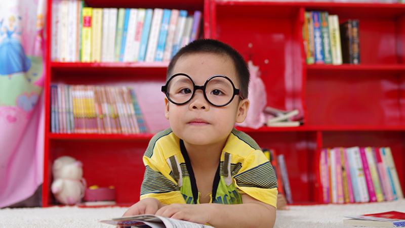 small boy in library reading a book