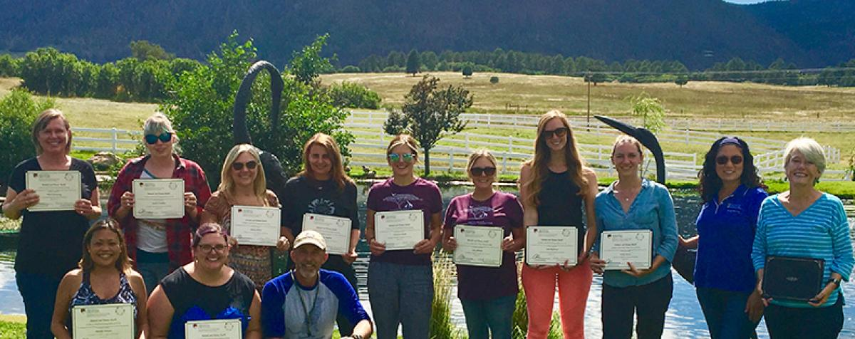 AHH Graduates with Certificates in front of the Rockies