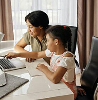 child and mother by a laptop