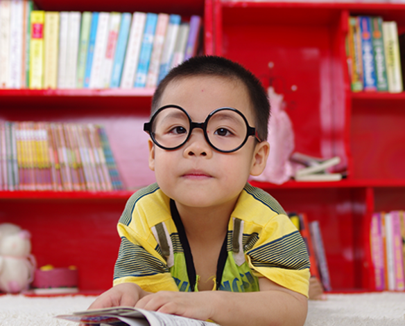 small boy in library reading a book​