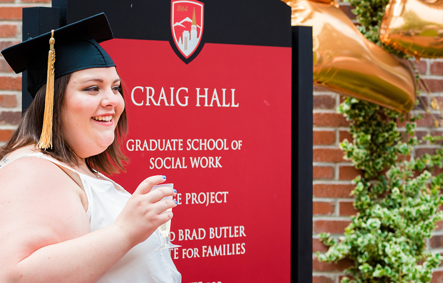 MSW graduate by Craig Hall sign
