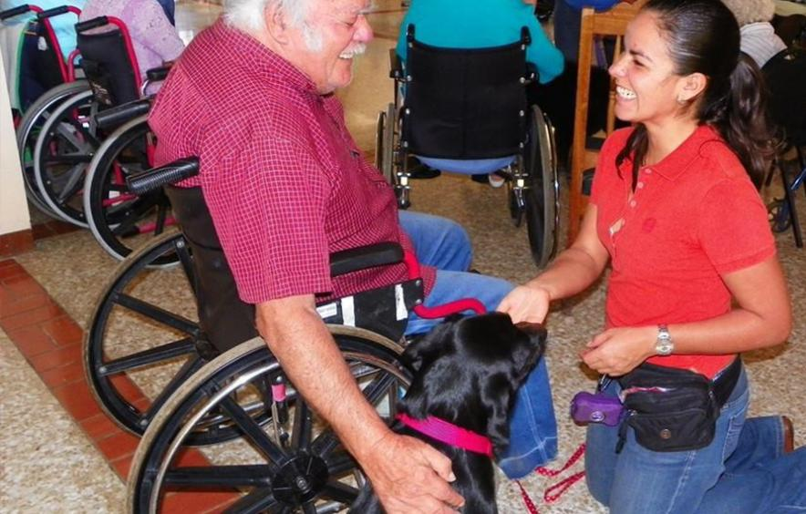 Woman with therapy dog and man in wheelchair