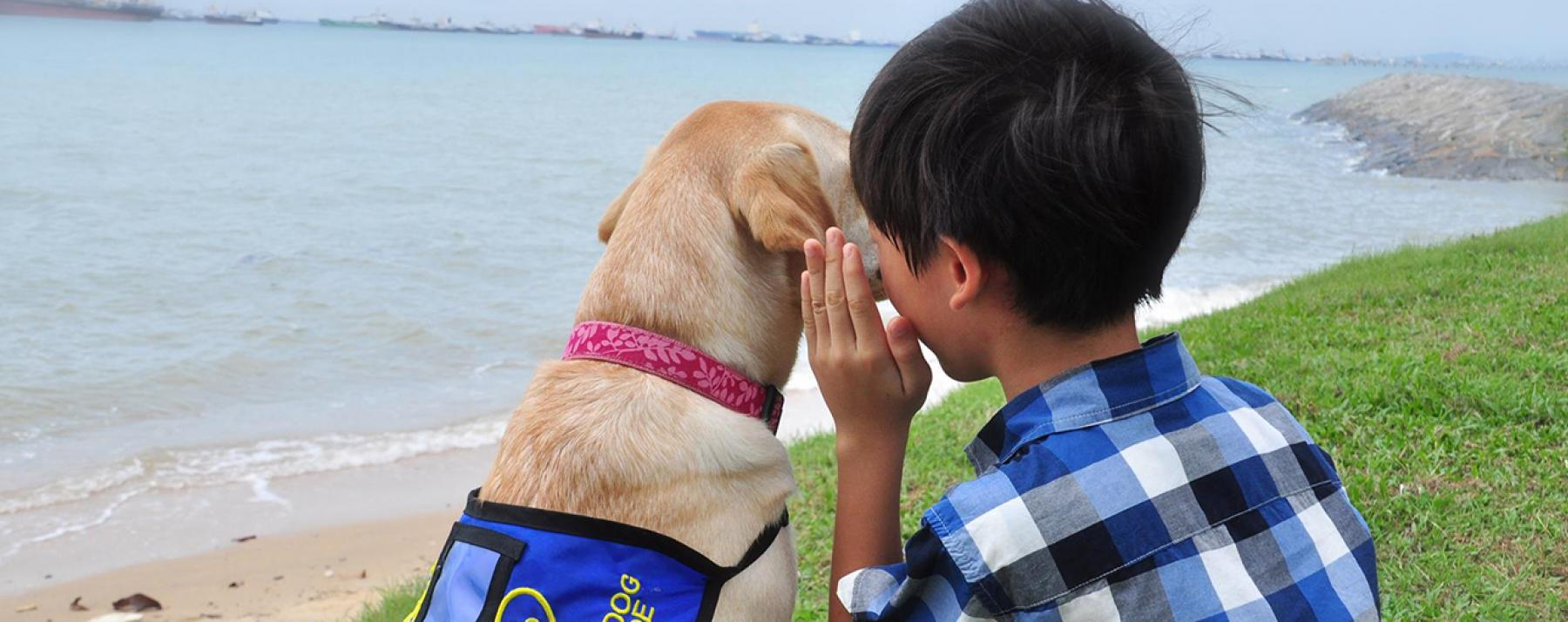 Boy telling dog a secret