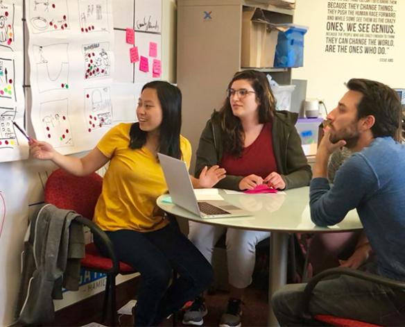 Human-centered design student Mae Thompson, BA '18, shares her work with design consultants.